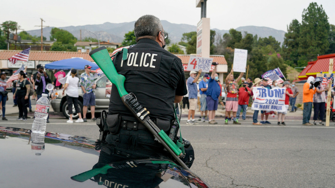 A Los Angeles police officer faces Trump supporters during a pro-Trump rally in Tujunga.