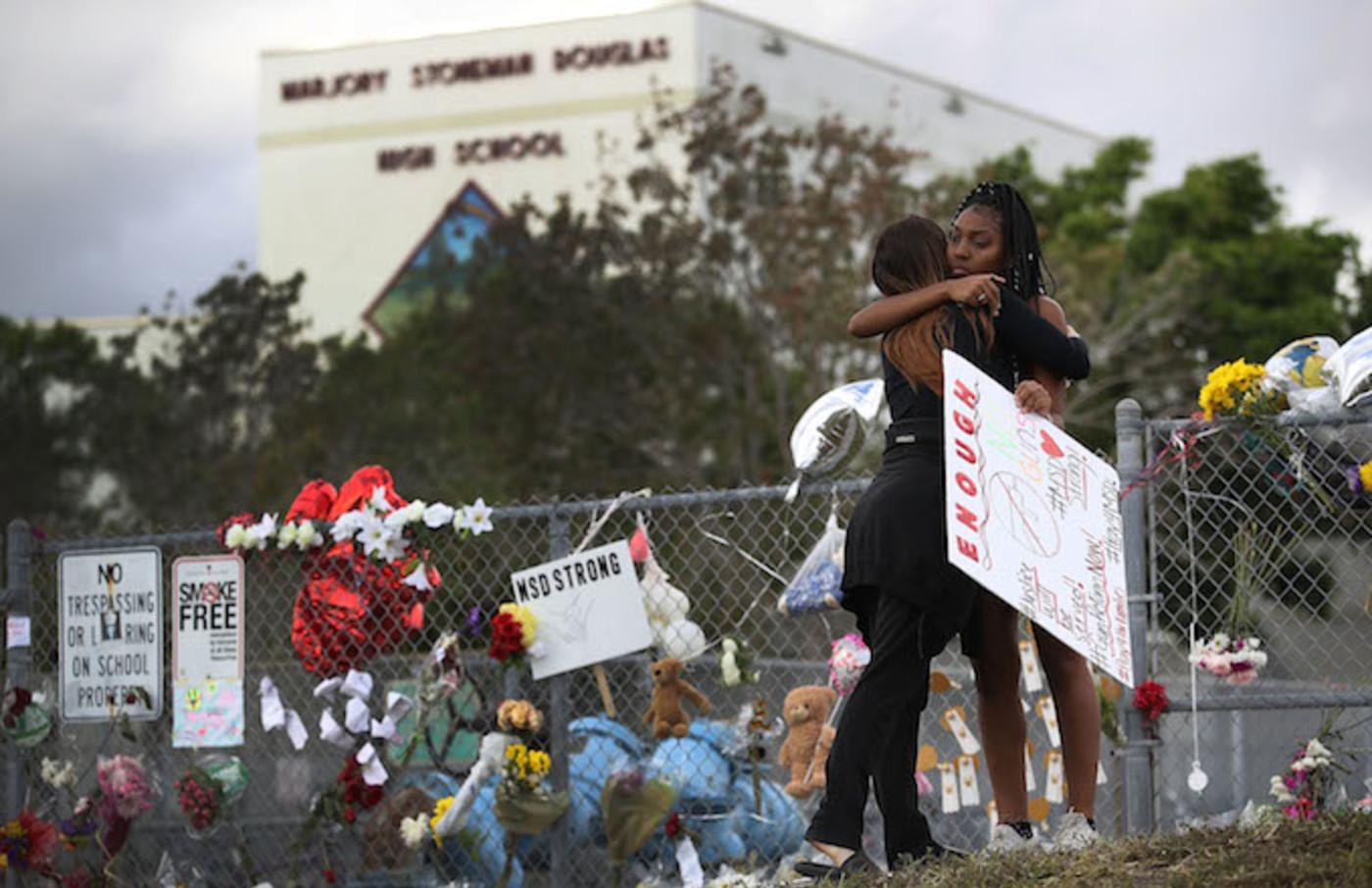 Two  Marjory Stoneman Douglas High School embracing in front of school.