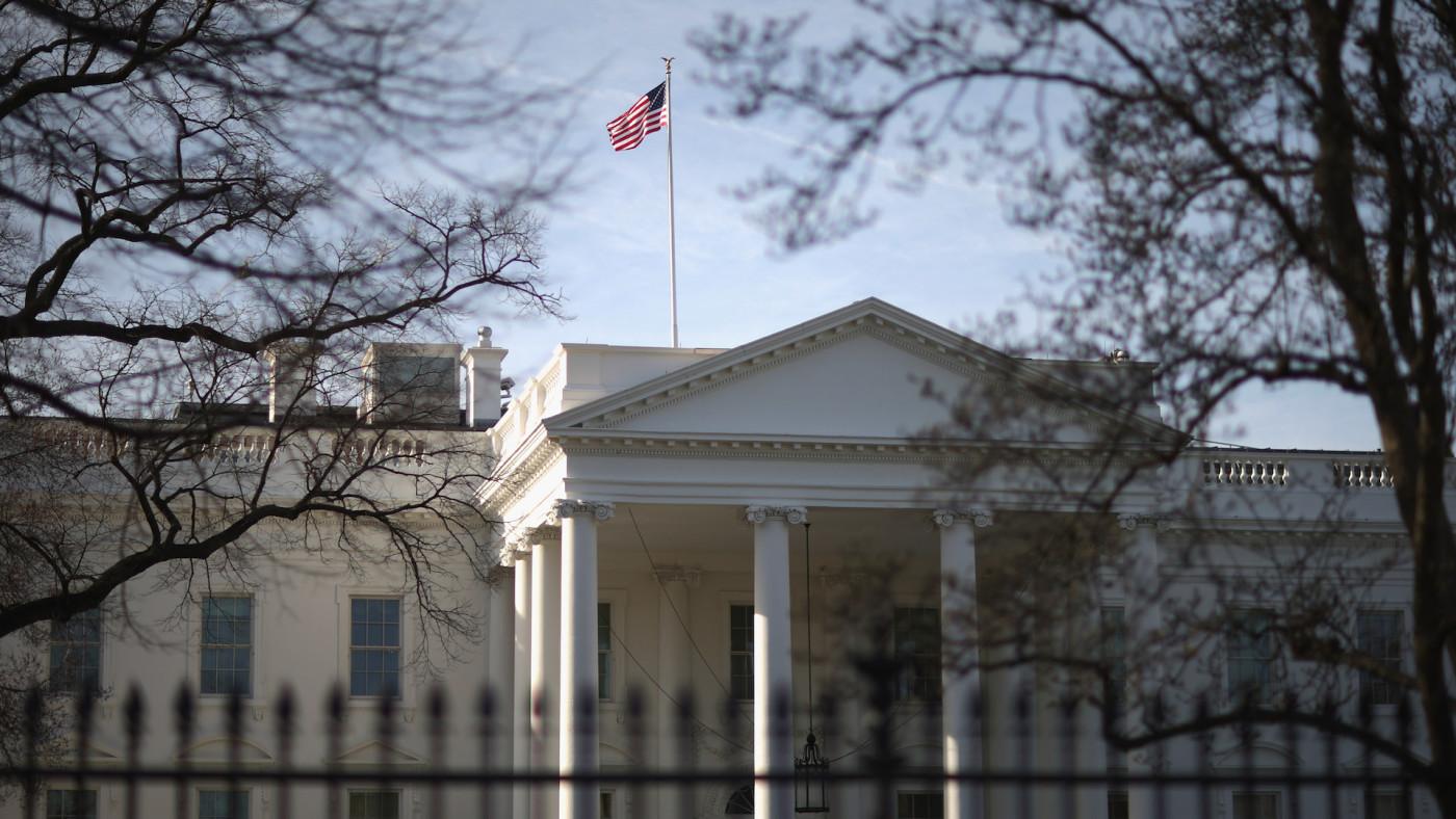 Morning sunlight strikes the flag flying above the White House.