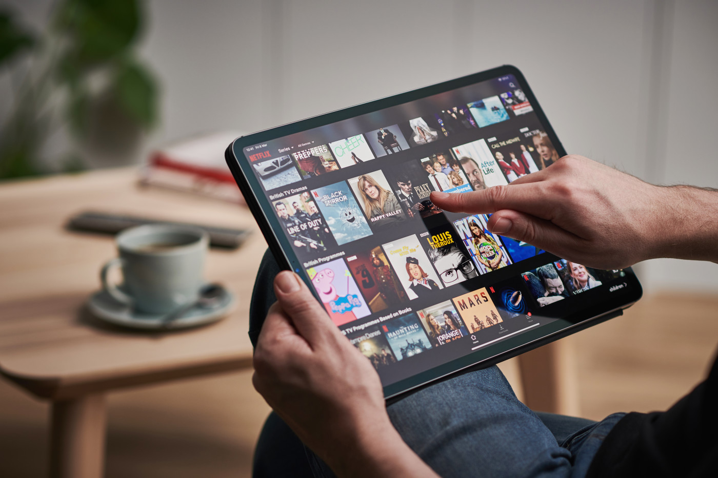 Hands holding iPad Pro with Netflix selection on screen