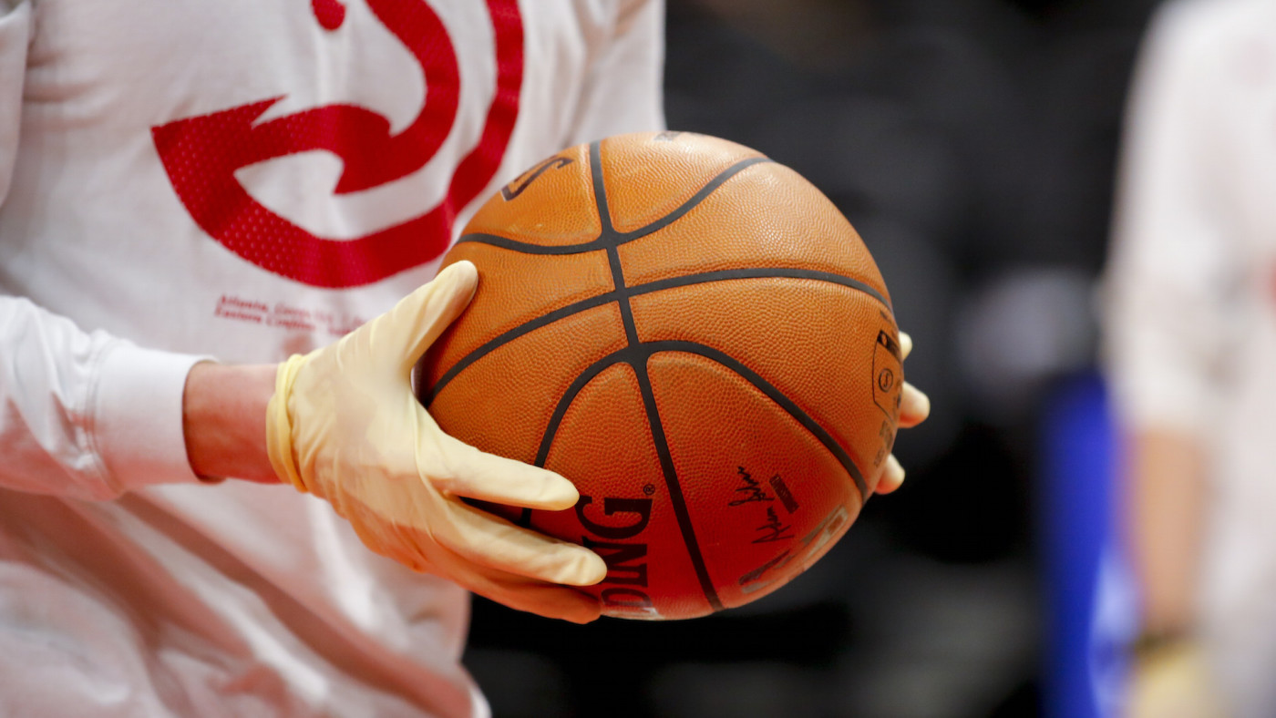 Ballboys wear gloves while handling warmup basketballs