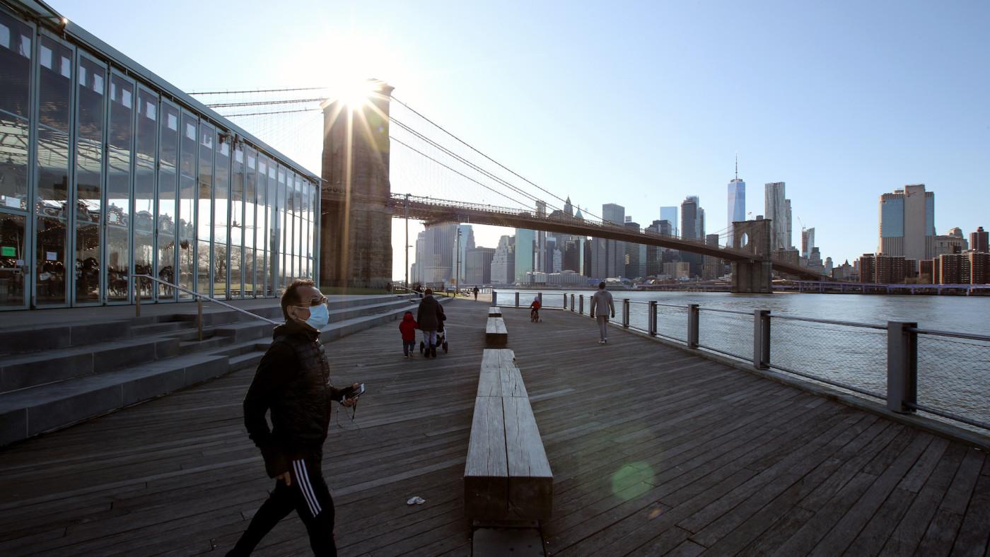 A pedestrian wears protective face mask walking pier in Brooklyn's Dumbo neighborhood.