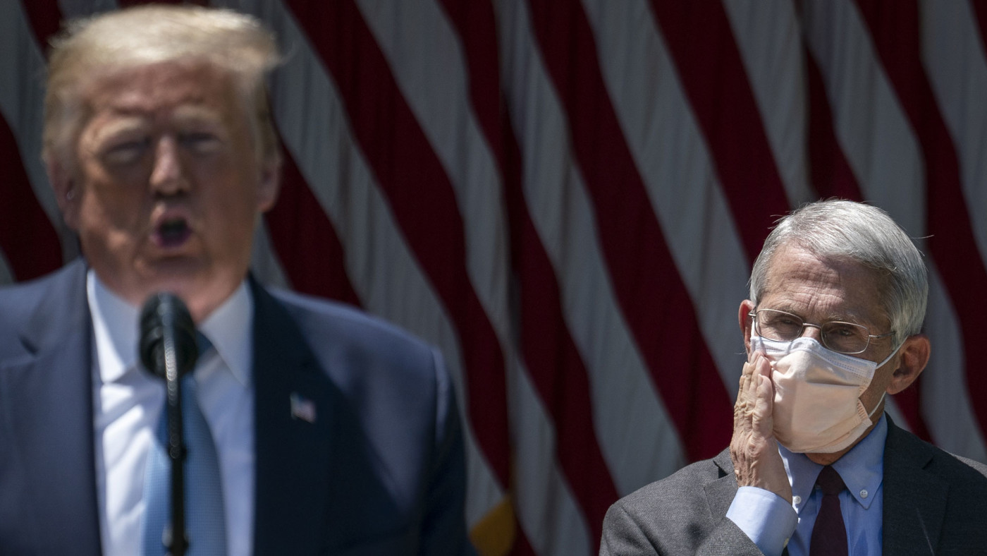 Donald Trump speaks as Anthony Fauci listens in the background.