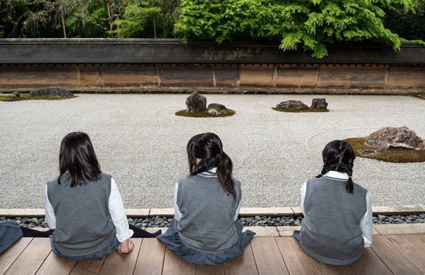 School-girls at zen rock garden, Ryoanji, Ryoan-ji Temple, Kyoto, Japan.