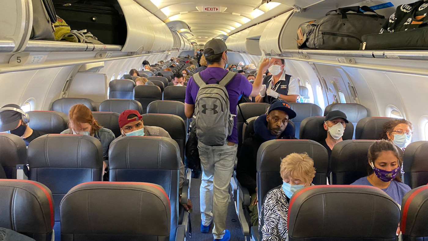 Passengers, almost all wearing facemasks, board an American Airlines flight.