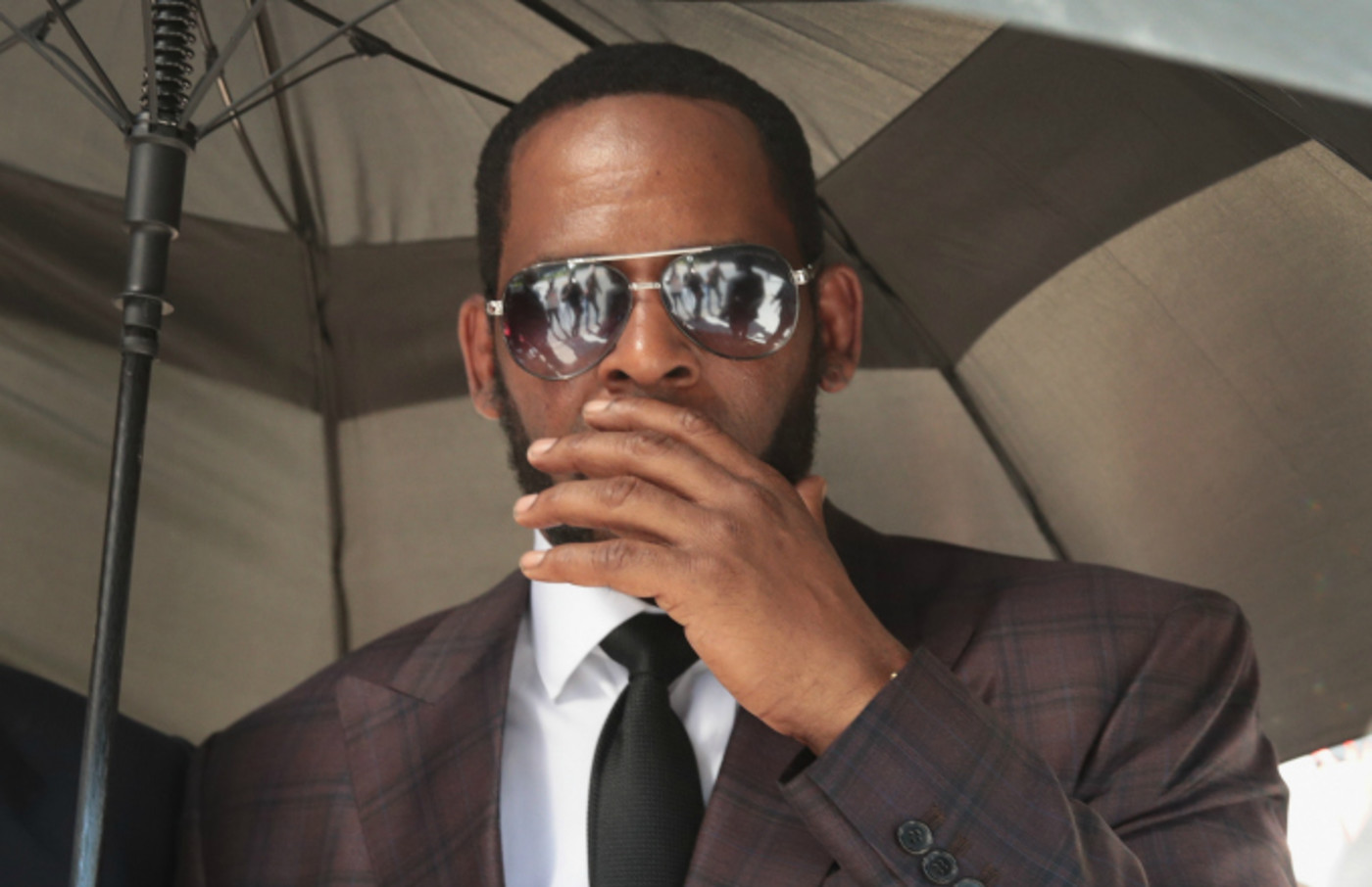 R&B singer R. Kelly covers his mouth