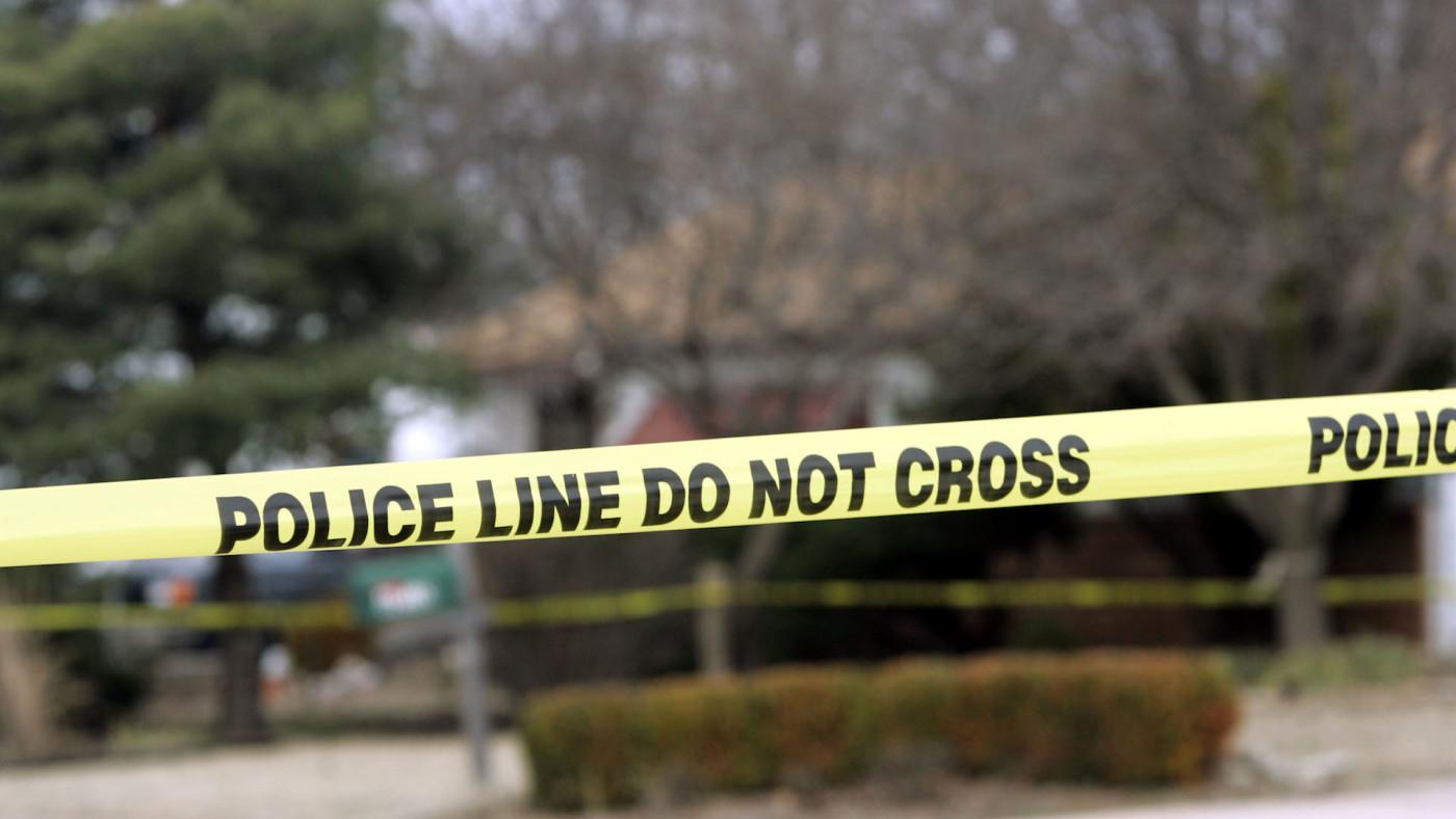 Police tape hangs across the street