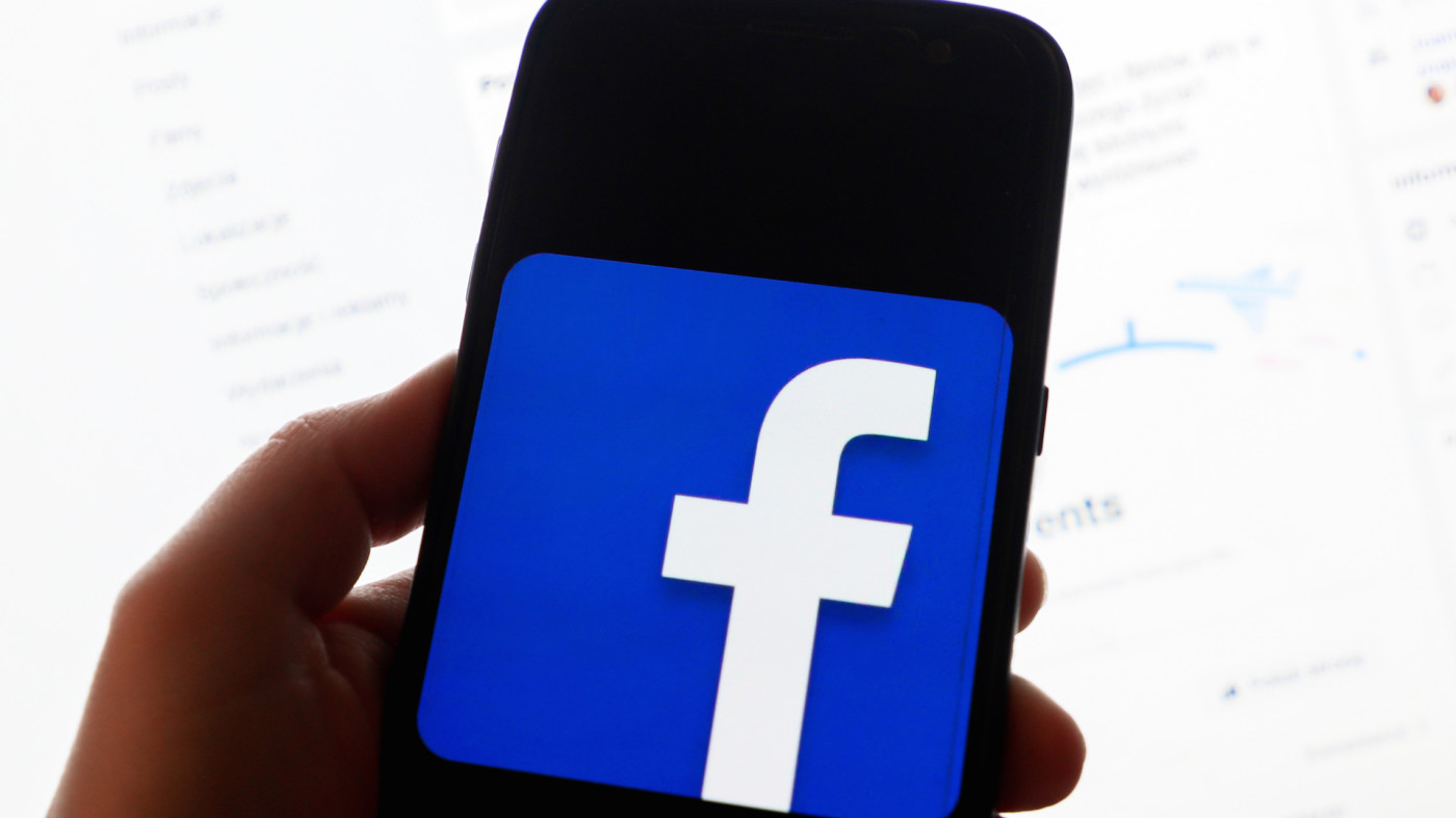 Facebook logo is displayed on a mobile phone screen