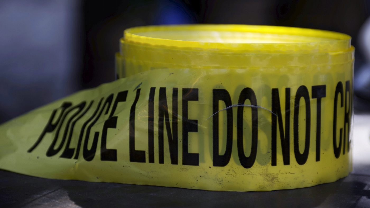 Roll of crime scene tape is unused as police officers interact with youth