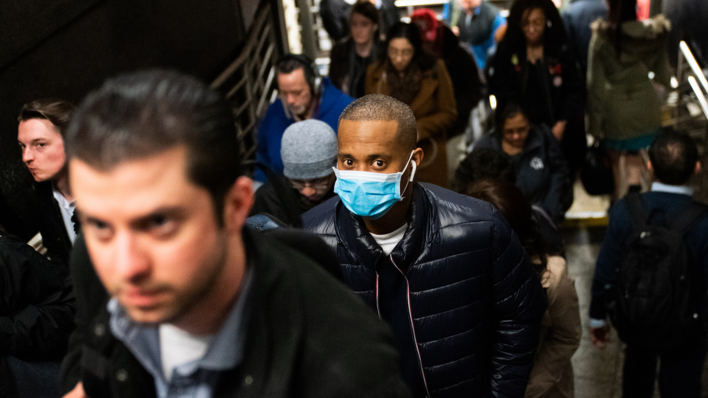A man wearing a protective mask is seen on a subway platform in New York City.