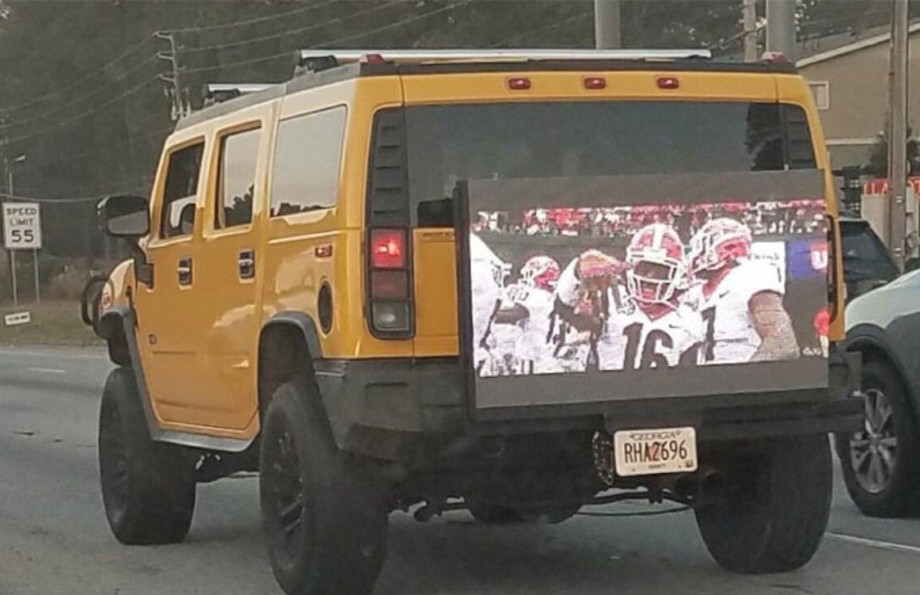 A cocky Georgia fan plays the SEC Championship Game on the back of his Hummer.