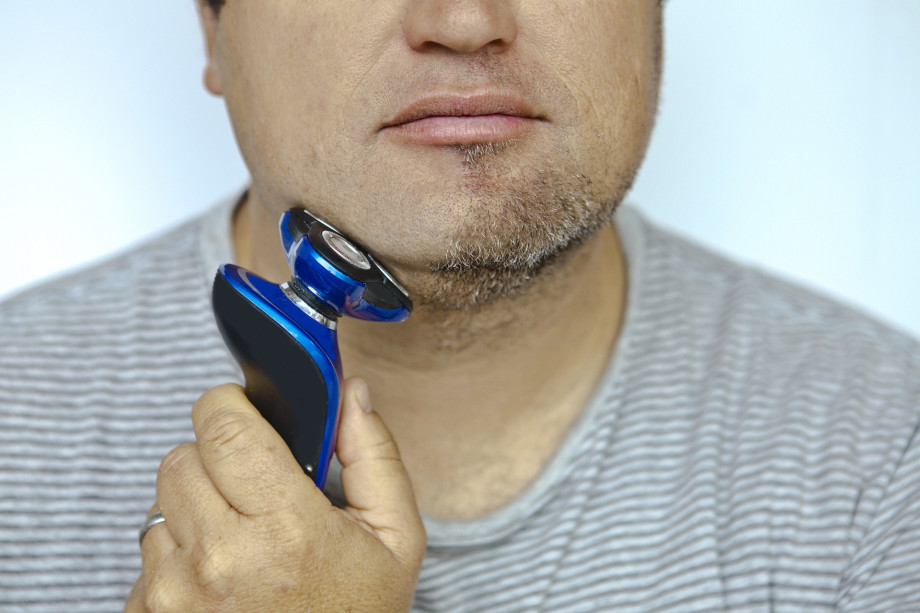 Man shaving using an electric razor.