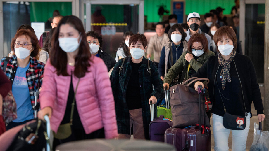 Passengers getting off a flight with face masks on.