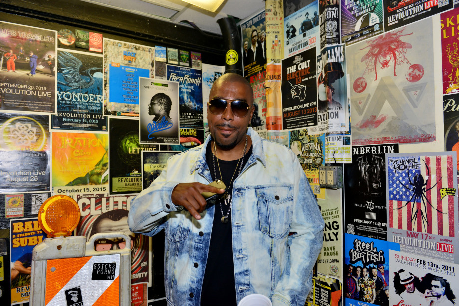 Noreaga/N.O.R.E. in denim jacket, black shirt and sunglasses in front of wall of posters