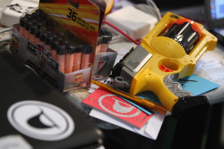 A Pirate Party logo sticker is seen on a laptop next to a Nerf toy dart gun lying on a table.