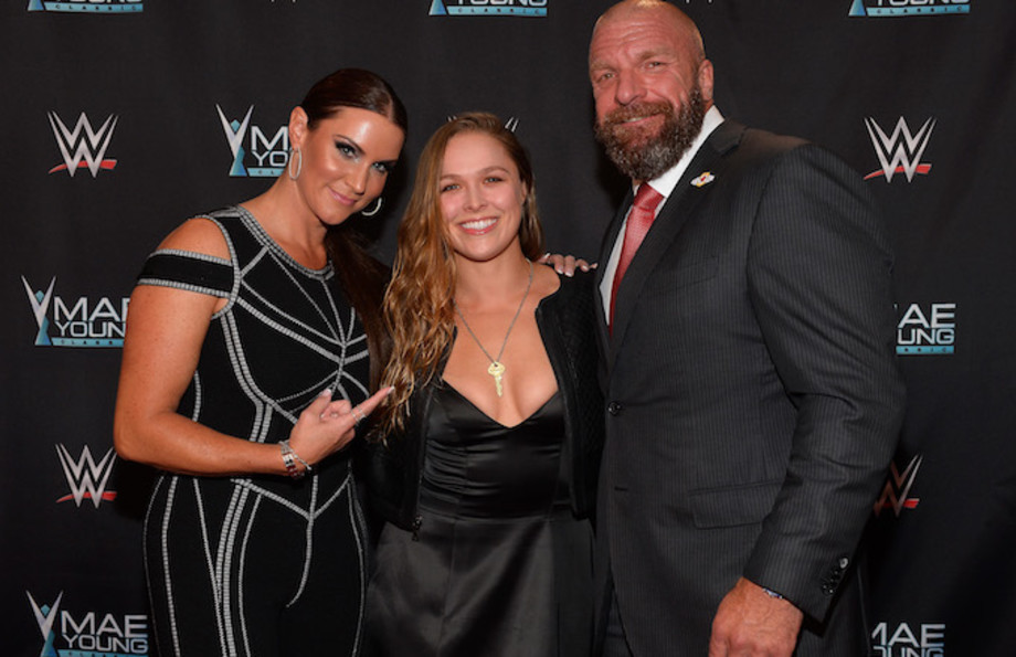 Stephanie McMahon, Ronda Rousey, and Triple H appear on the red carpet.