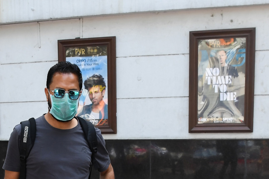 A man wearing a facemask walks pasts the closed Rivoli cinema complex in New Delhi