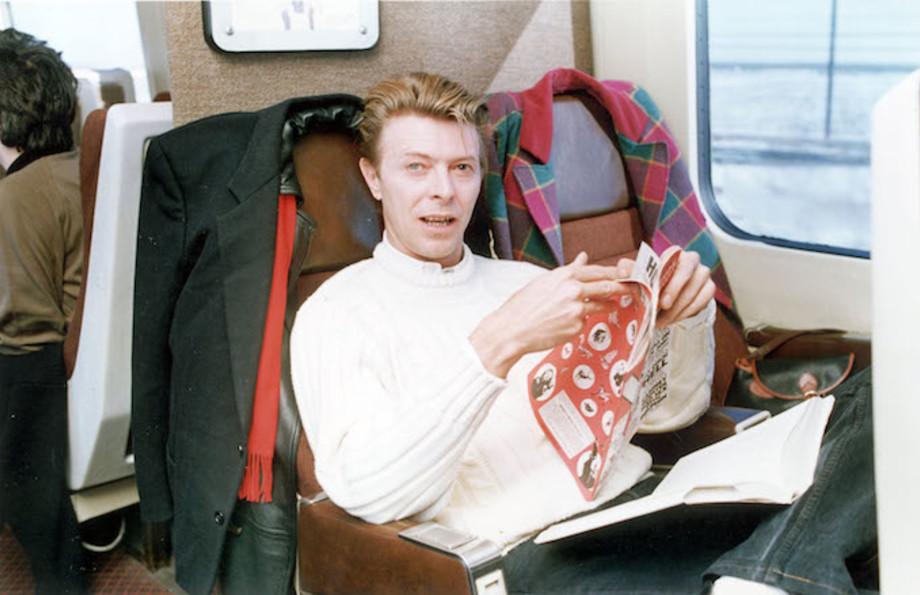 David Bowie circa 1990 reading a comic book on a train.