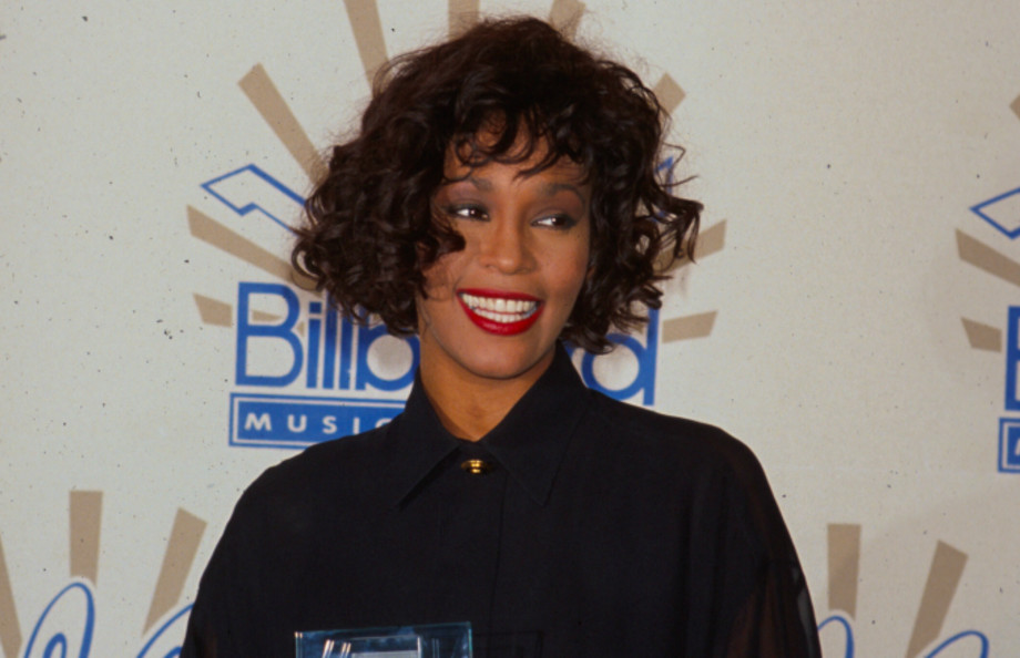 Singer Whitney Houston holding her award in Press Room at Billboard Music Awards