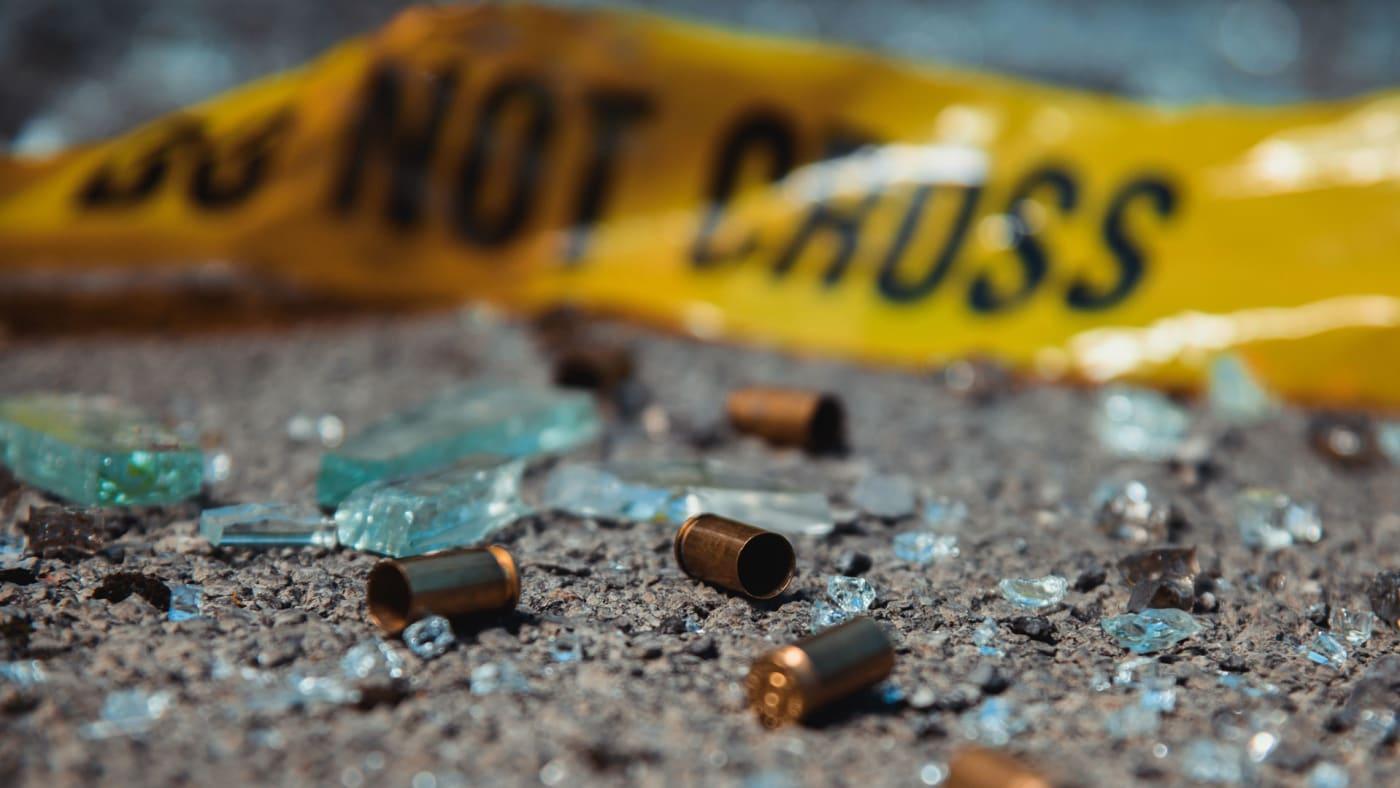 Bullet casings surround caution tape.
