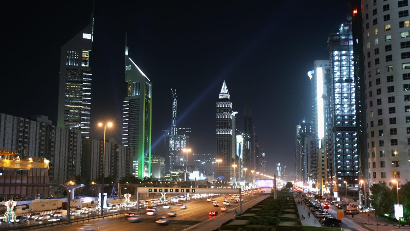 The iconic Emirates Towers dominate the skyline beside the wide boulevard of Sheikh Zayed Road.