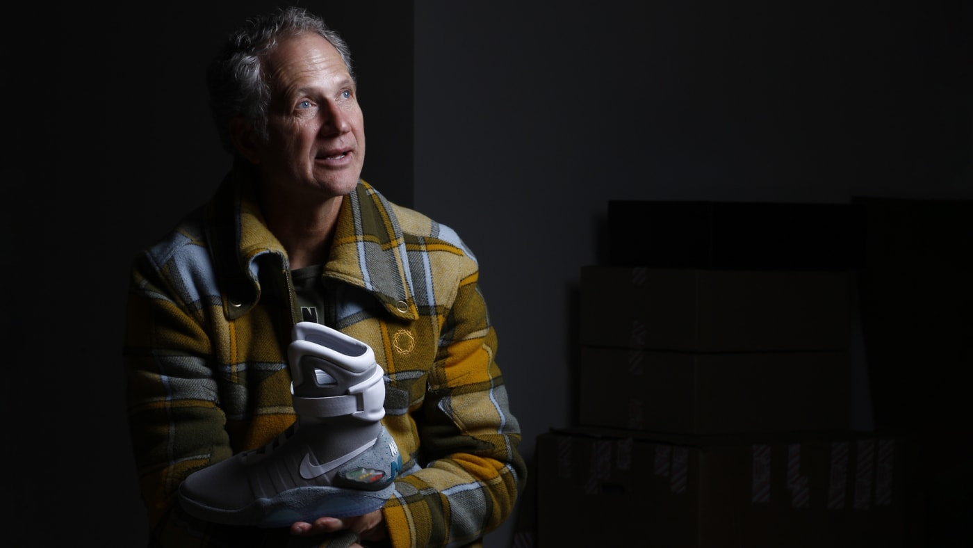 Nike designer Tinker Hatfield holding the Back to the Future Nike Mag shoes he designed