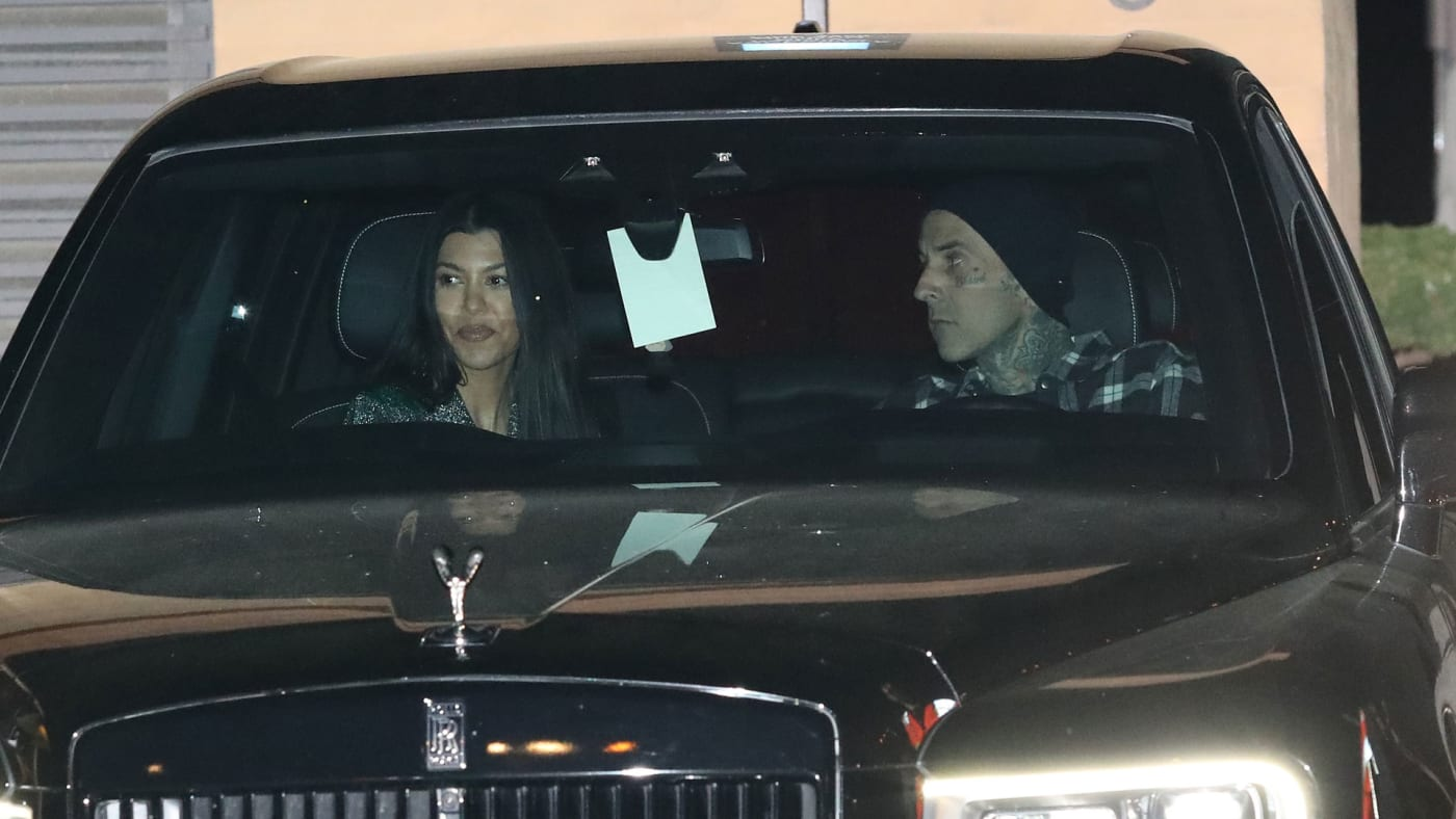 Kourtney Kardashian and Travis Barker being hounded by the paparazzi.