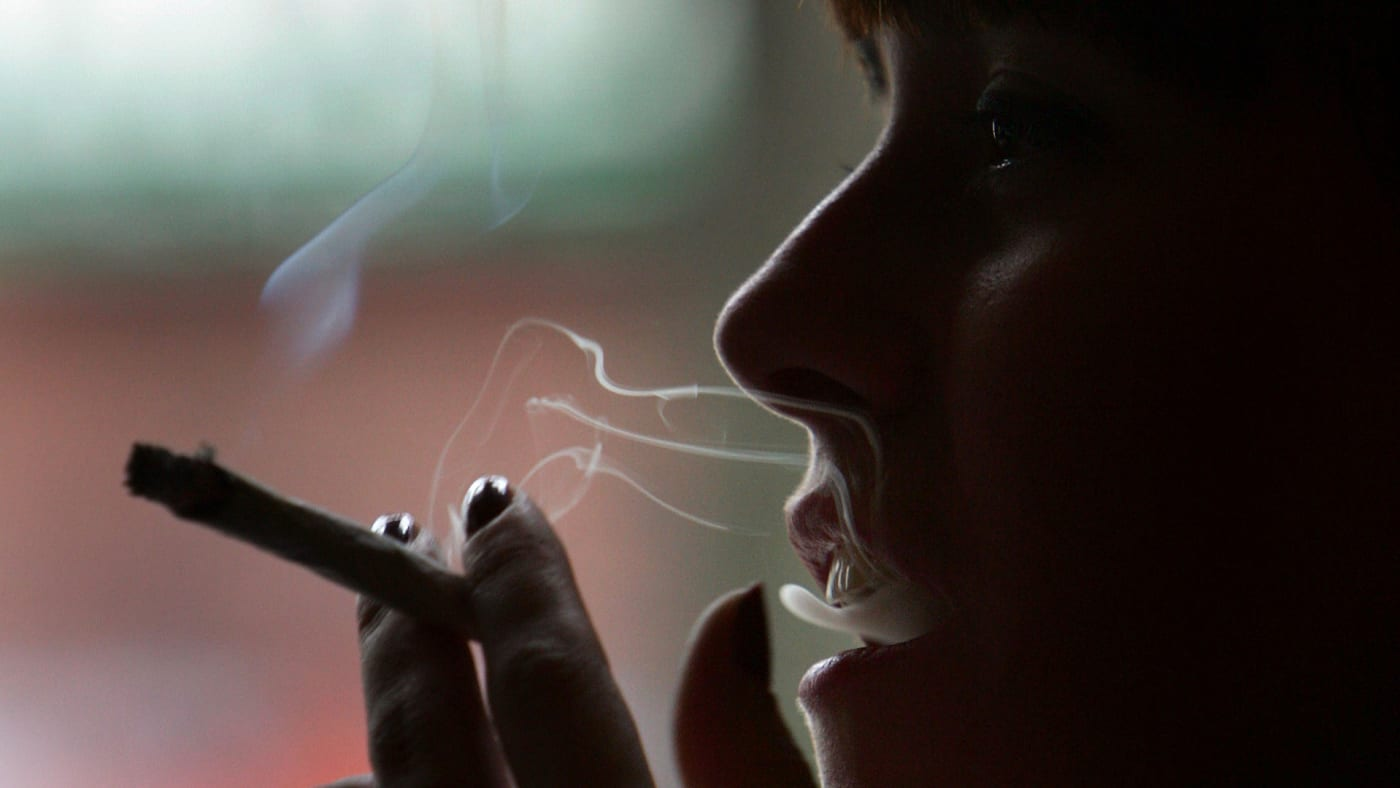 A woman smokes a cigarette of marijuana in an Amsterdam cafe.