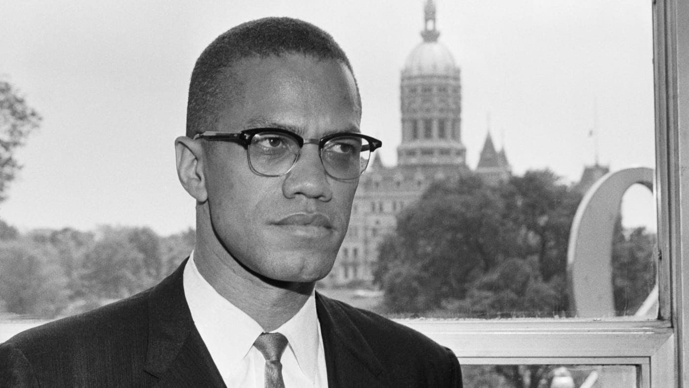 Malcolm X, is shown with the dome of the Connecticut Capitol behind him.