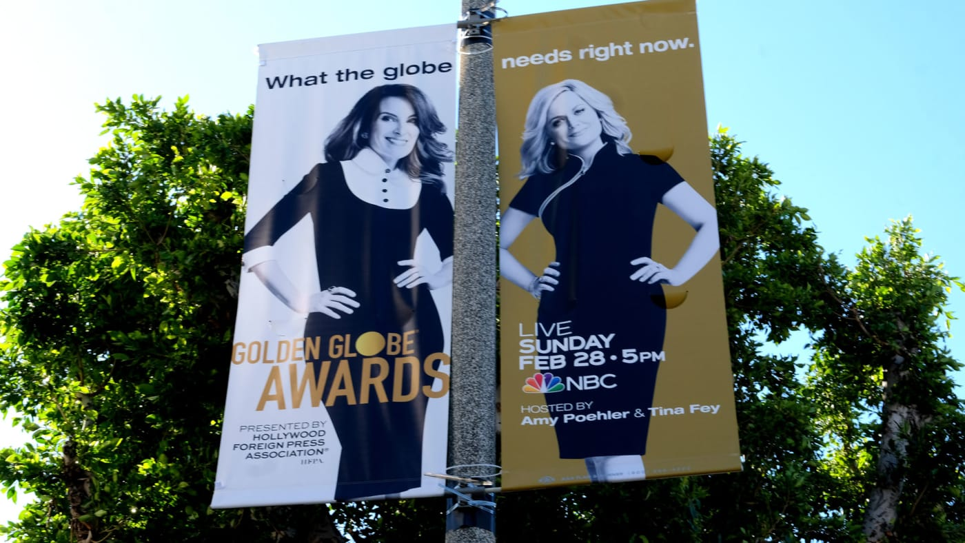 A sign advertises Tina Fey and Amy Poehler hosting the 2021 Golden Globes.