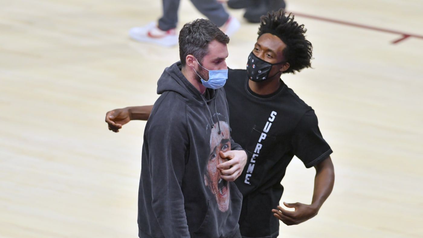 Kevin Love and Collin Sexton joke on the sidelines.