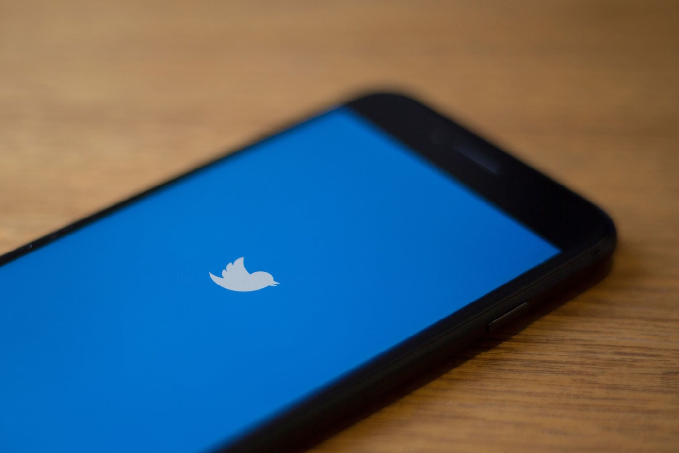 The Twitter logo is seen on a phone in this photo illustration in Washington, DC.