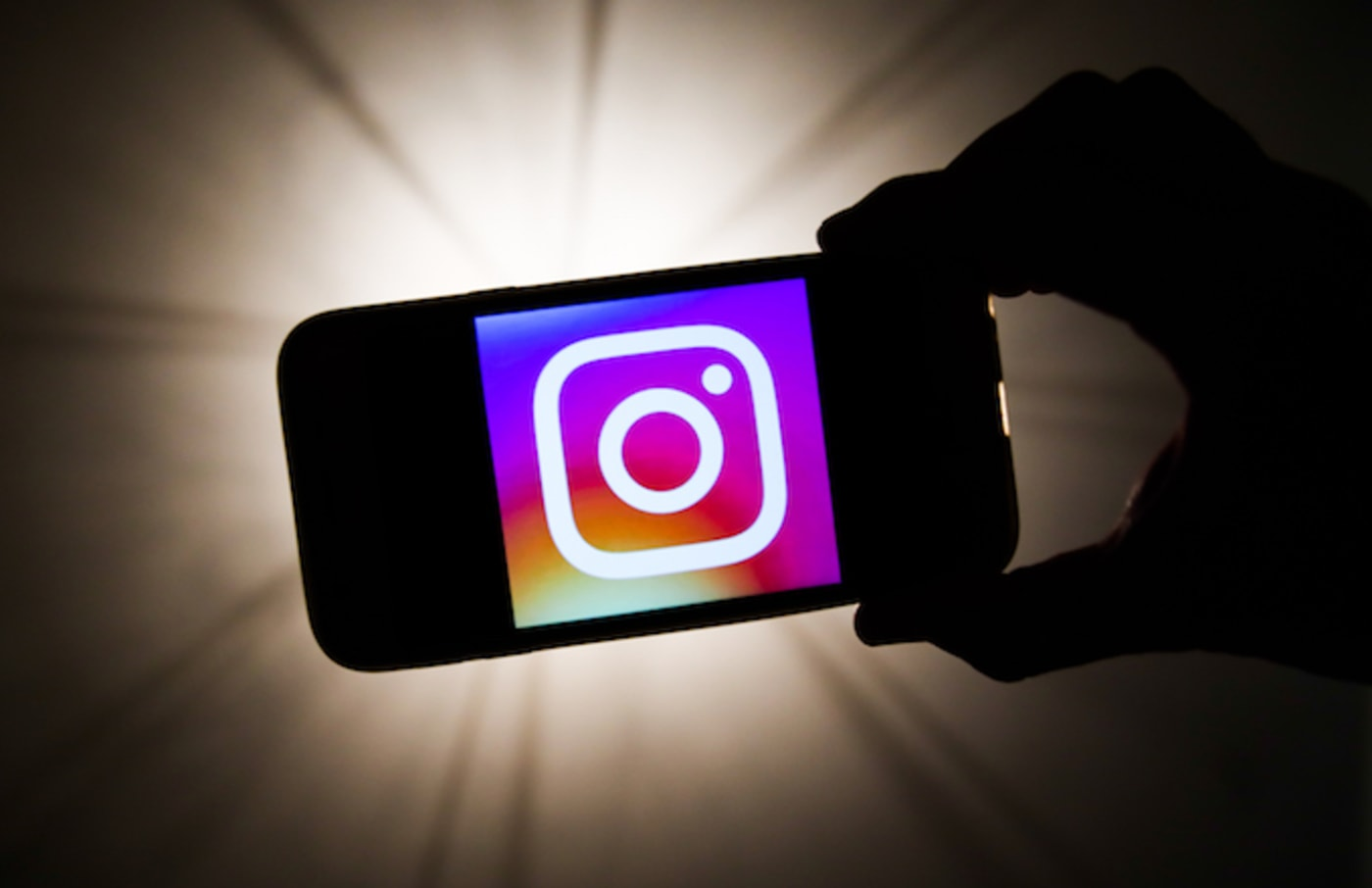 Instagram logo is seen displayed on a phone screen.