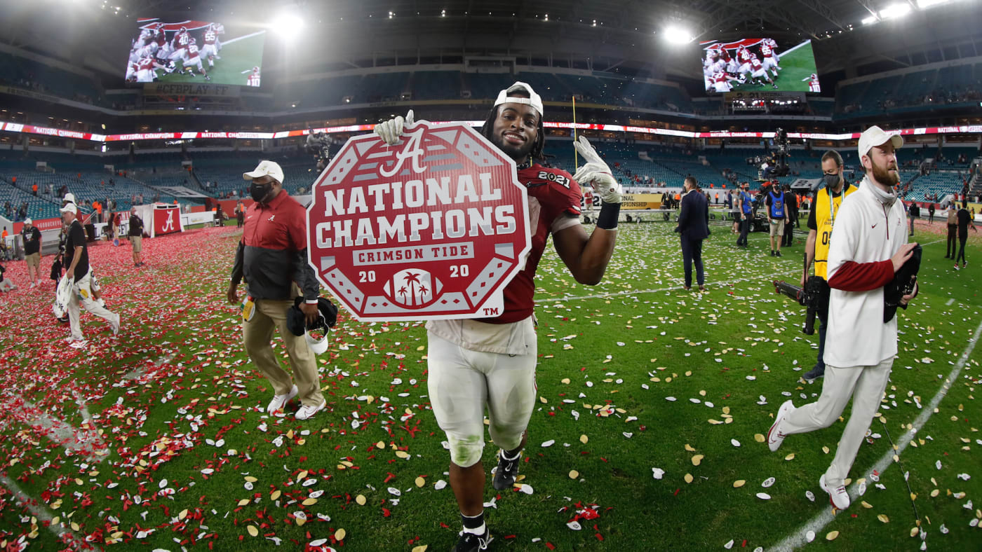 Najee Harris #22 of the Alabama Crimson Tide holds a National Champions sign