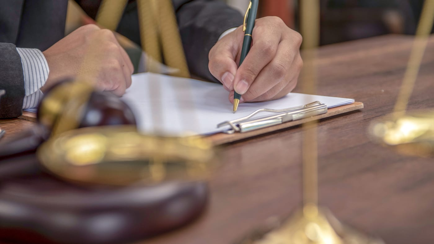 A legal official is seen taking a pen to a court document.