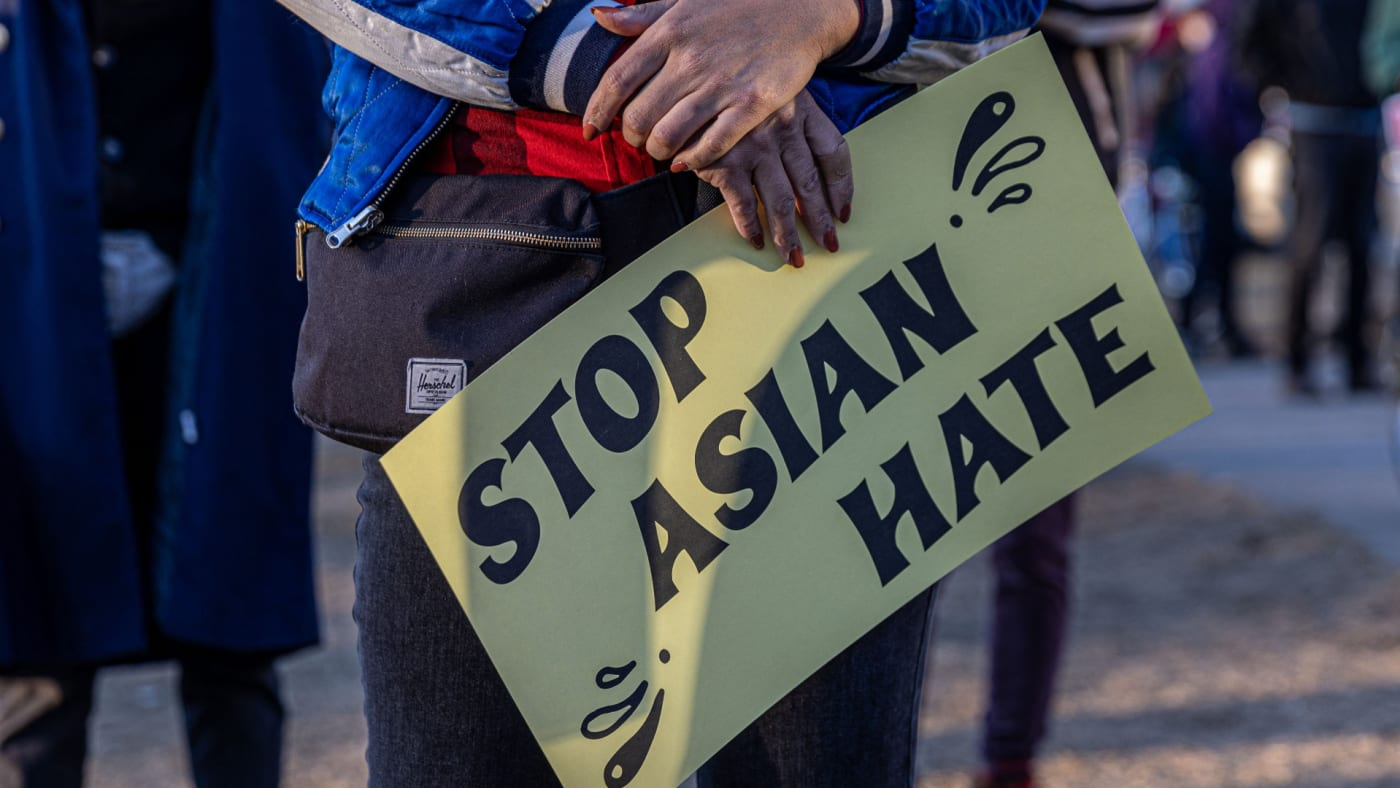 """A person holds a sign during the """"Asian Solidarity March"""" rally."""