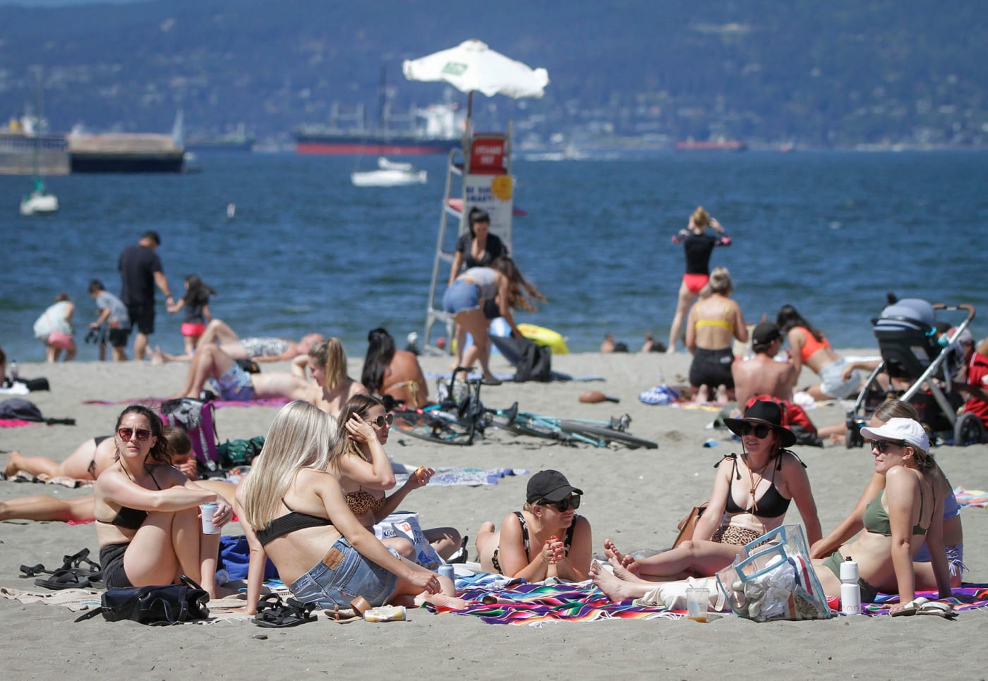 People enjoy their leisure time under the hot weather warning at Kitsilano Beach in Vancouver, Canada,