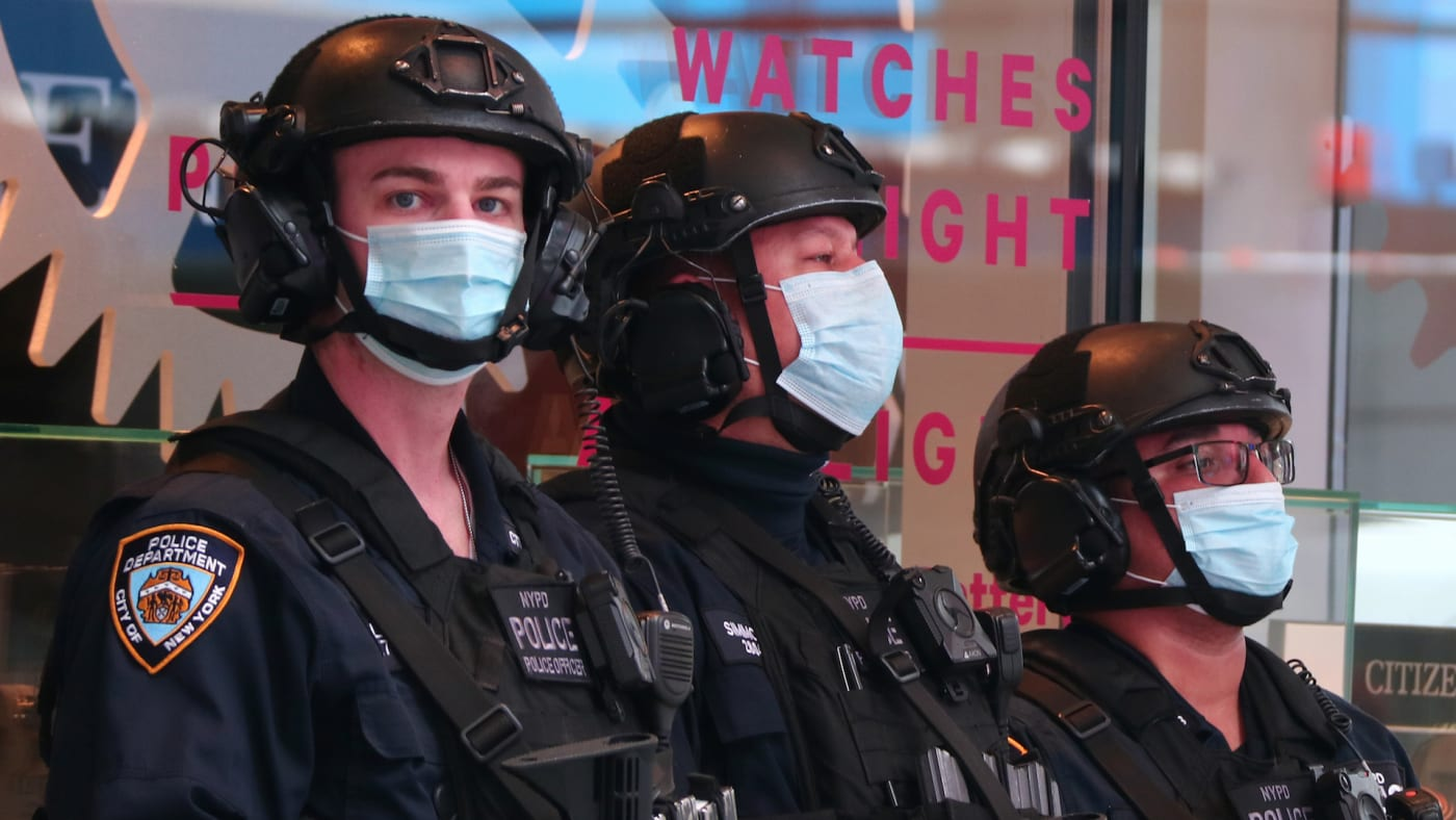 NYPD police officers wear masks as they stand guard in Times Square