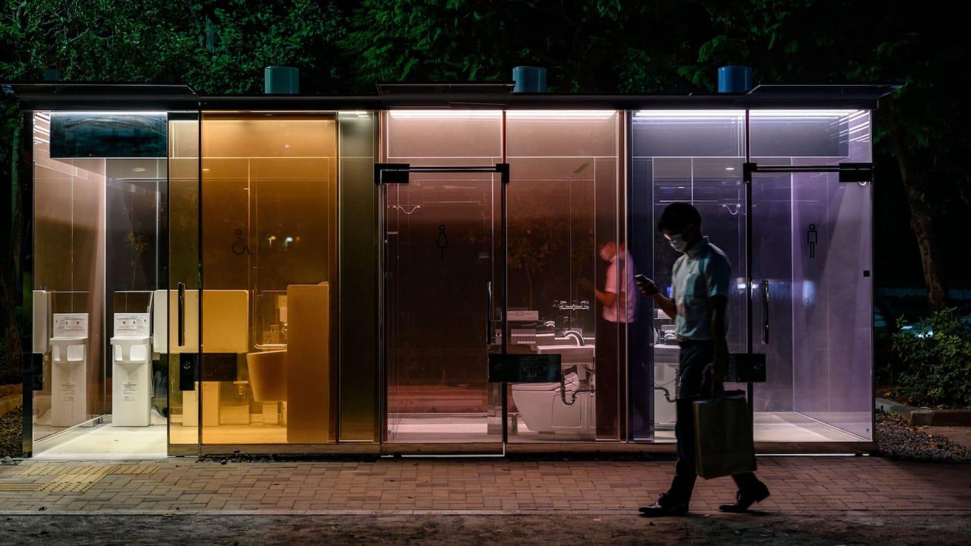A man walks past a transparent toilet designed by Shigeru Ban.