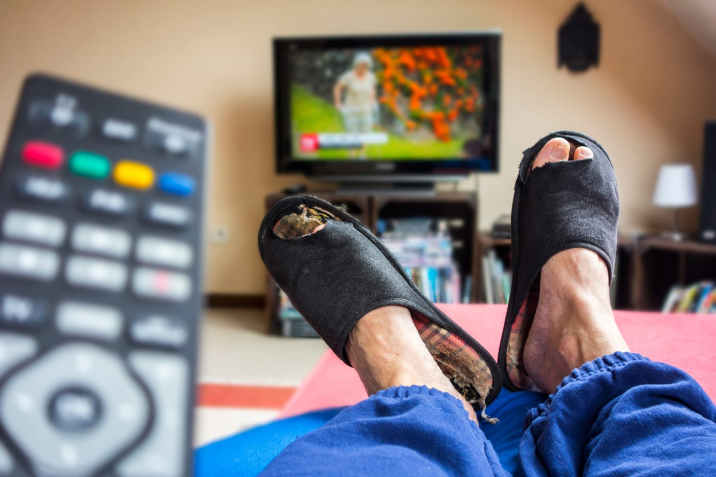 Remote control and couch potato, lazy man in comfy chair wearing worn slippers
