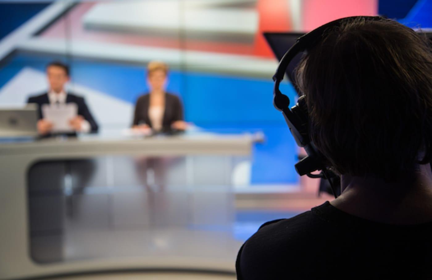 Cameraman filming news in television studio.