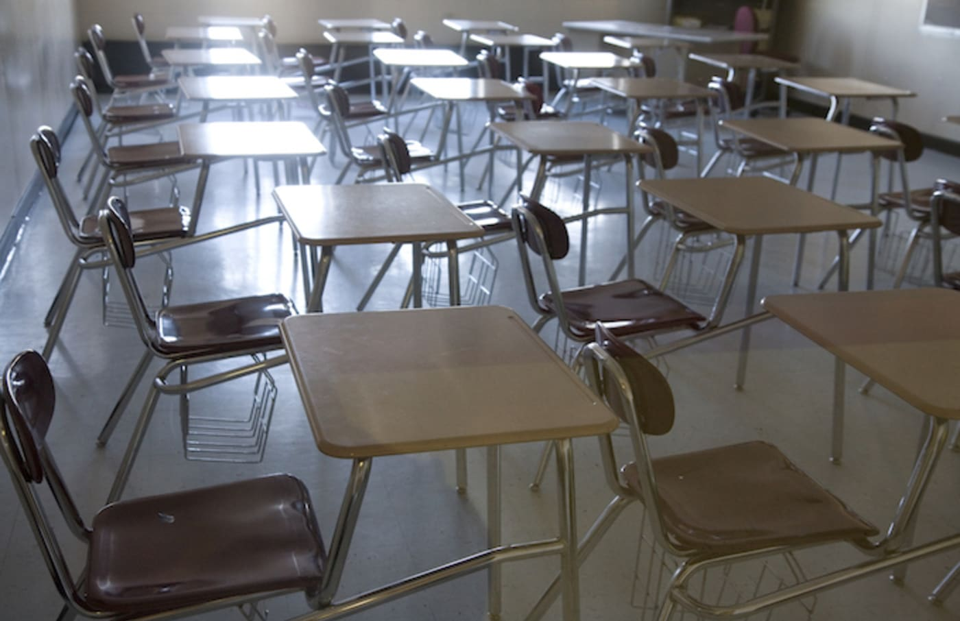 Empty chairs and desks in a high school classroom.