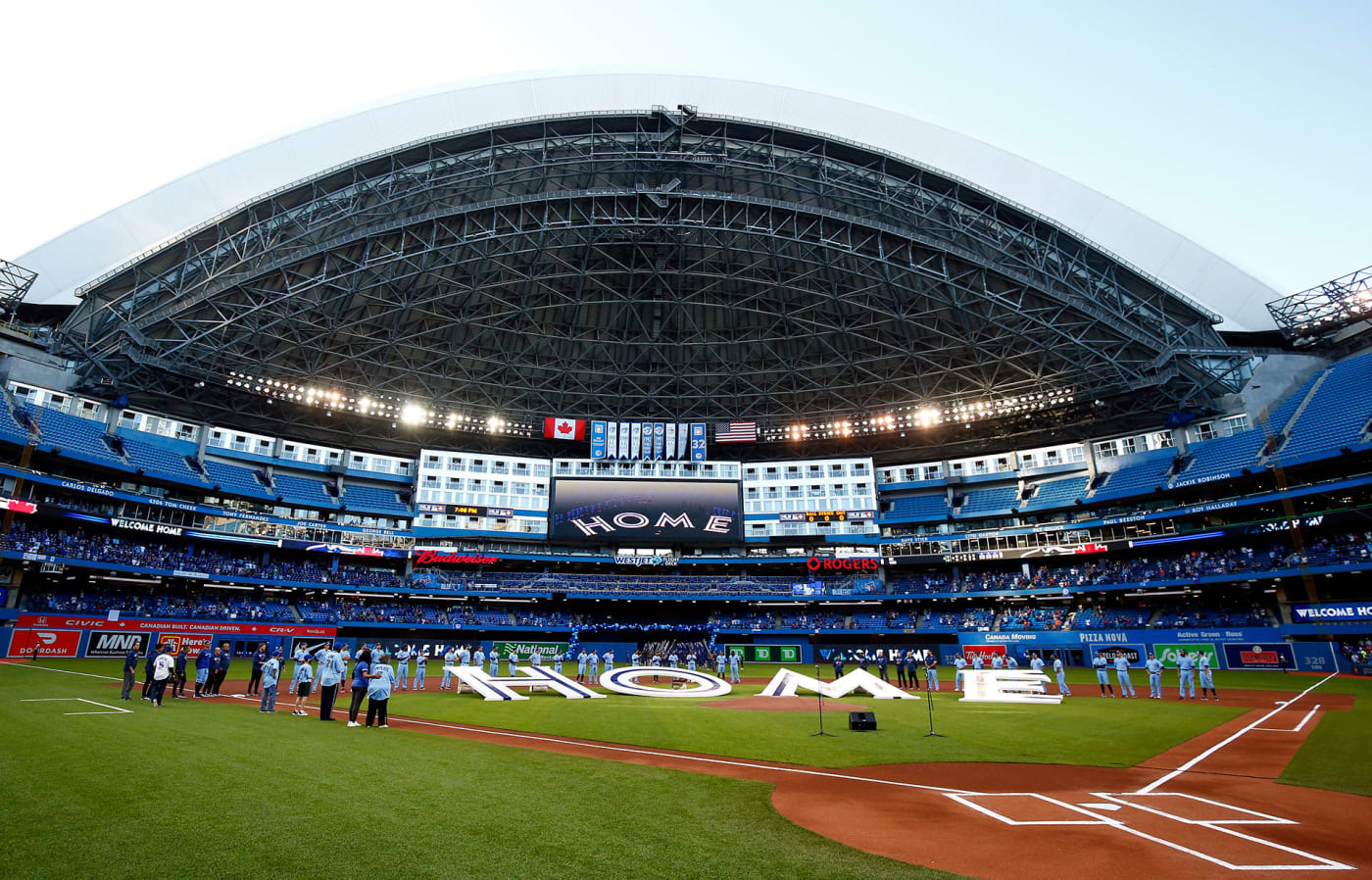 The Toronto Blue Jays line up behind a 'Home' sign to commemorate their first home game in Toronto this season prior to a MLB game against the Kansas City Royals at Rogers Centre on July 30, 2021 in Toronto, Canada.