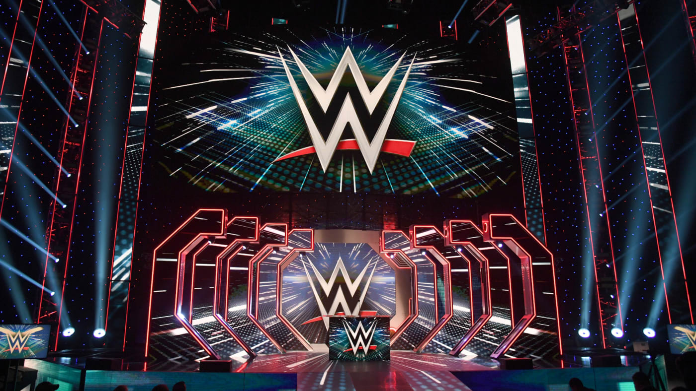 WWE logos are shown on screens before a WWE news conference.