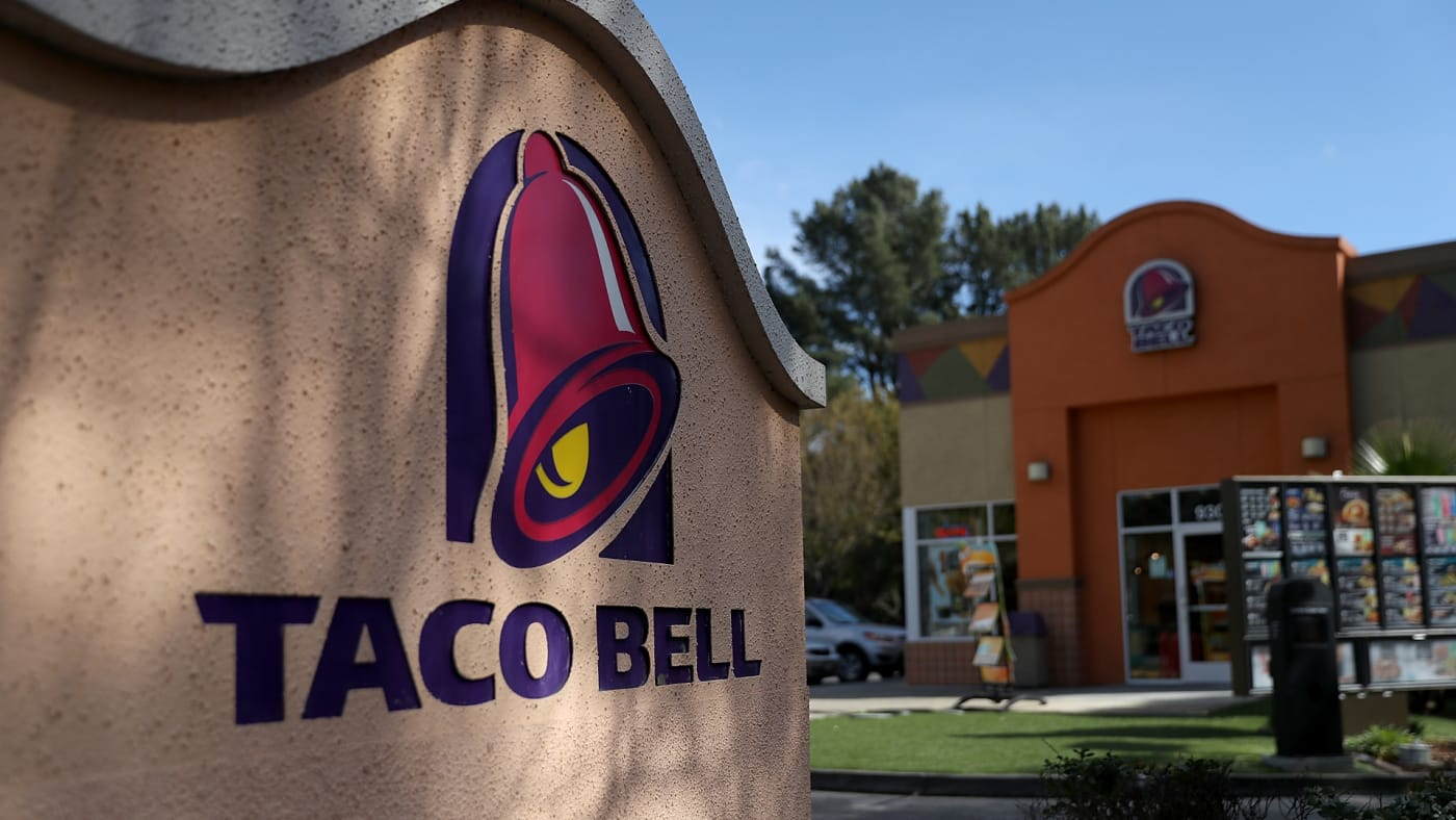 A sign is posted in front of a Taco Bell restaurant.