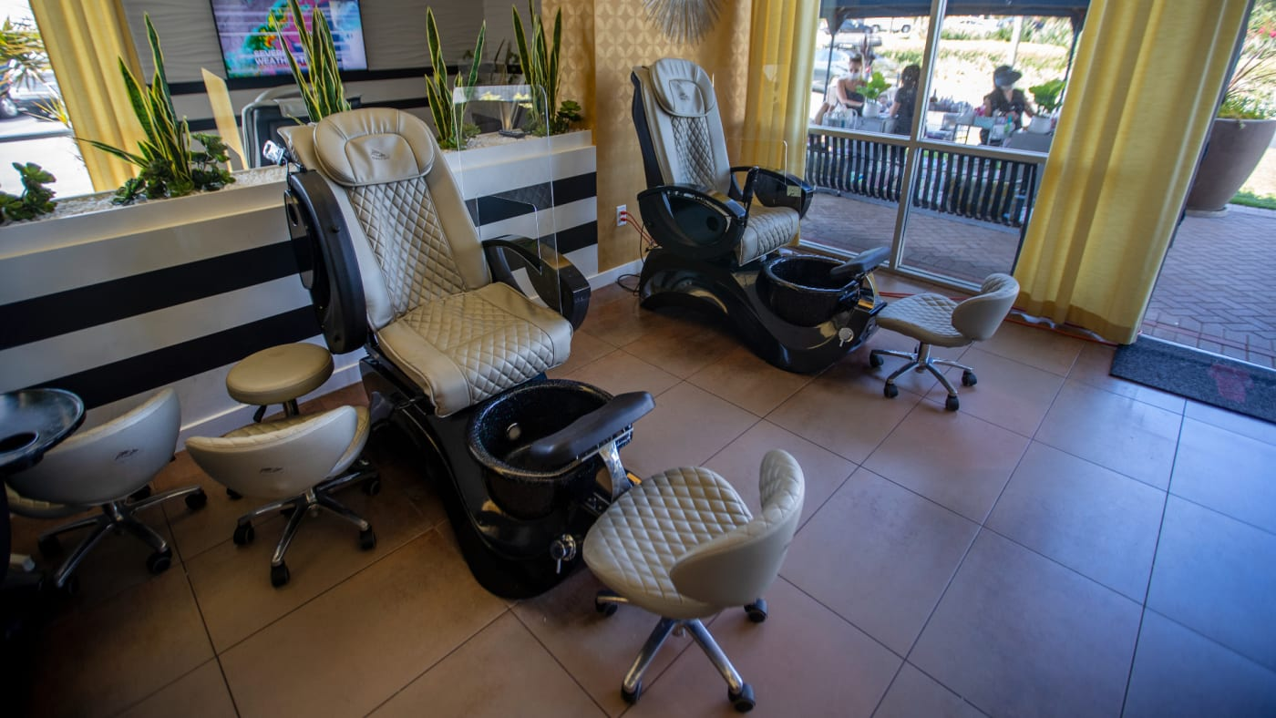 Inside chairs are empty as beauty technicians wear face masks while giving clients wearing face masks manicures and pedicures outdoors.