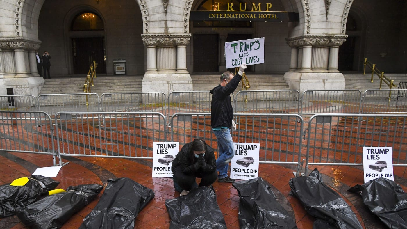 """The group calling themselves """"The People's Motorcade"""" , prays in front of the body bags"""