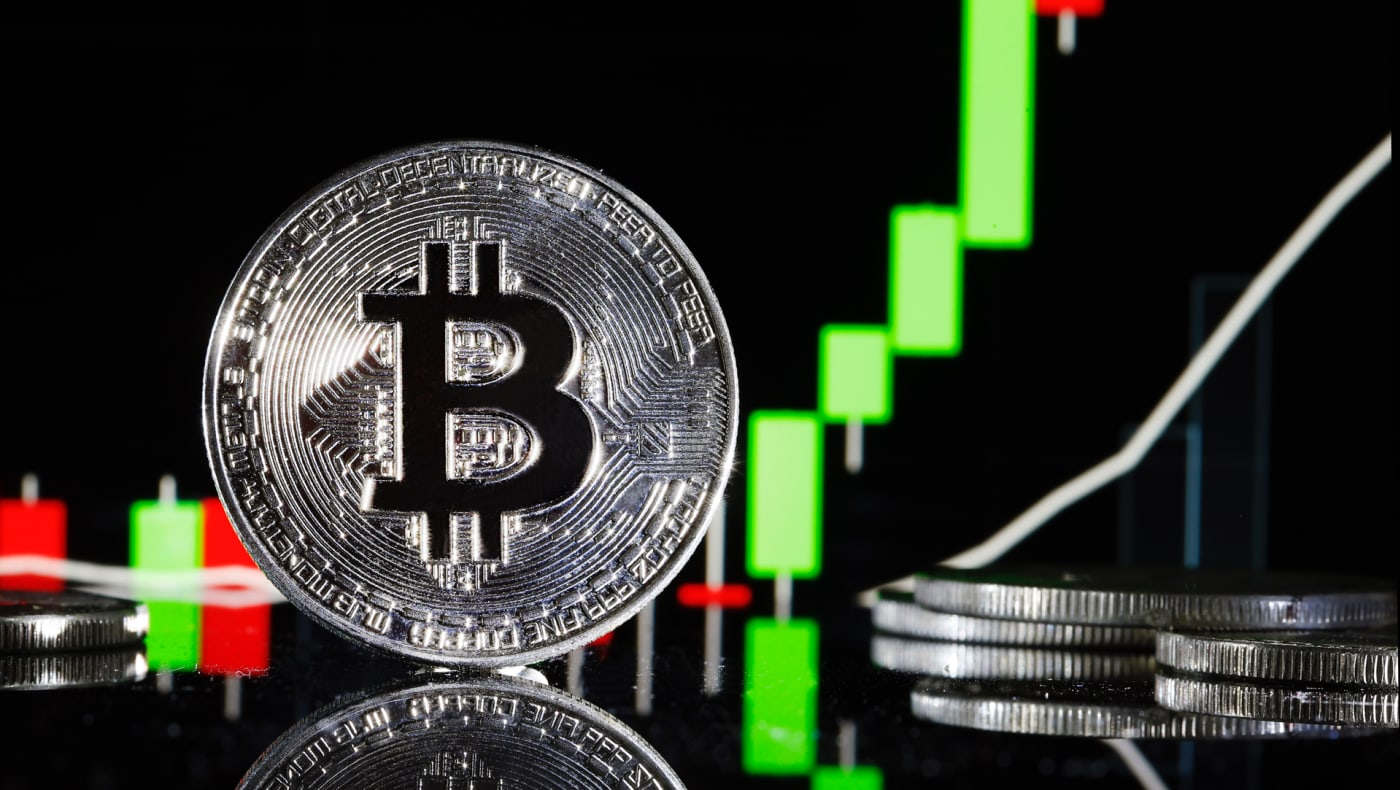 Bitcoin novelty coin in front of trading report