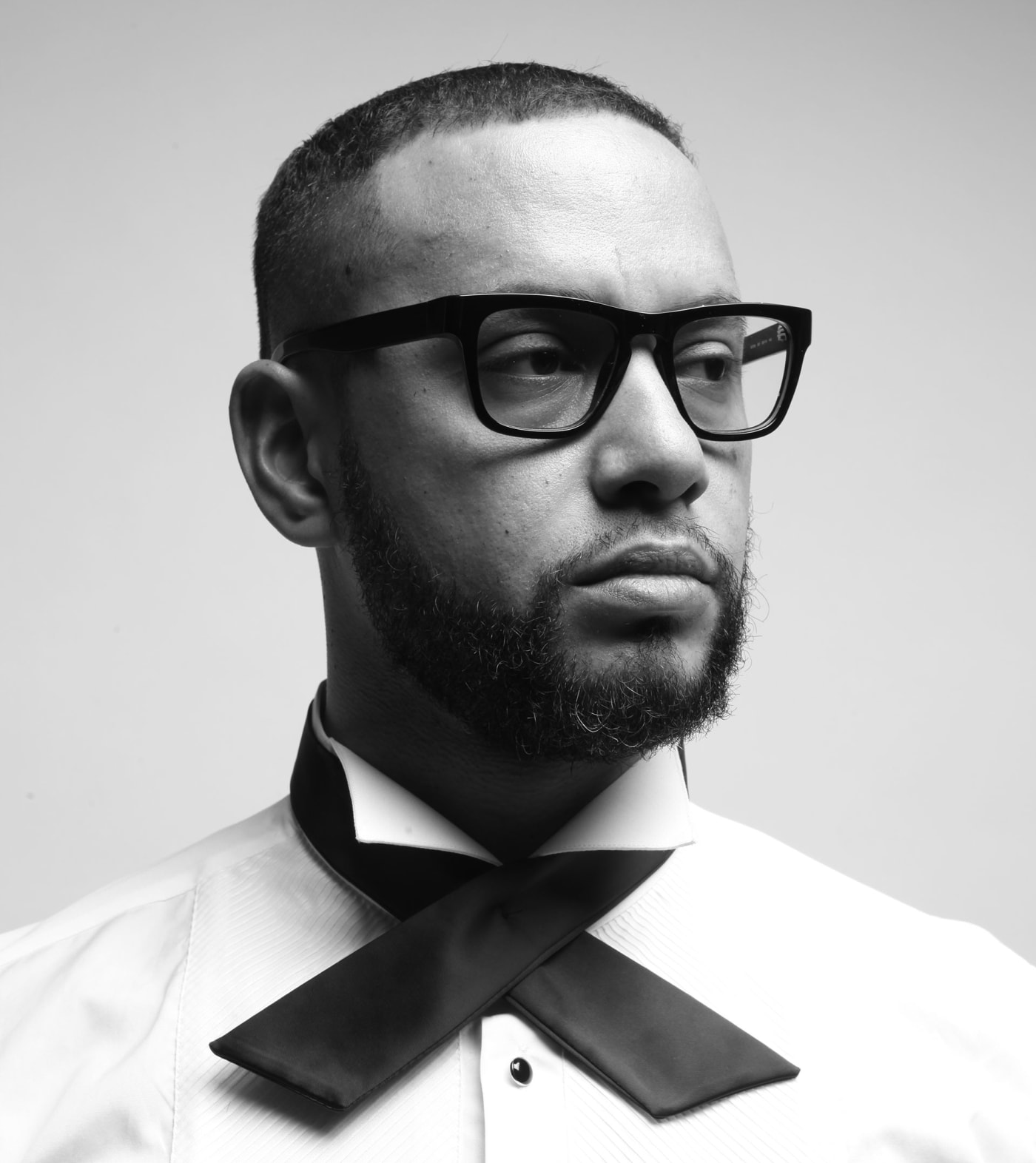Director X poses in a white shirt and x shaped tie