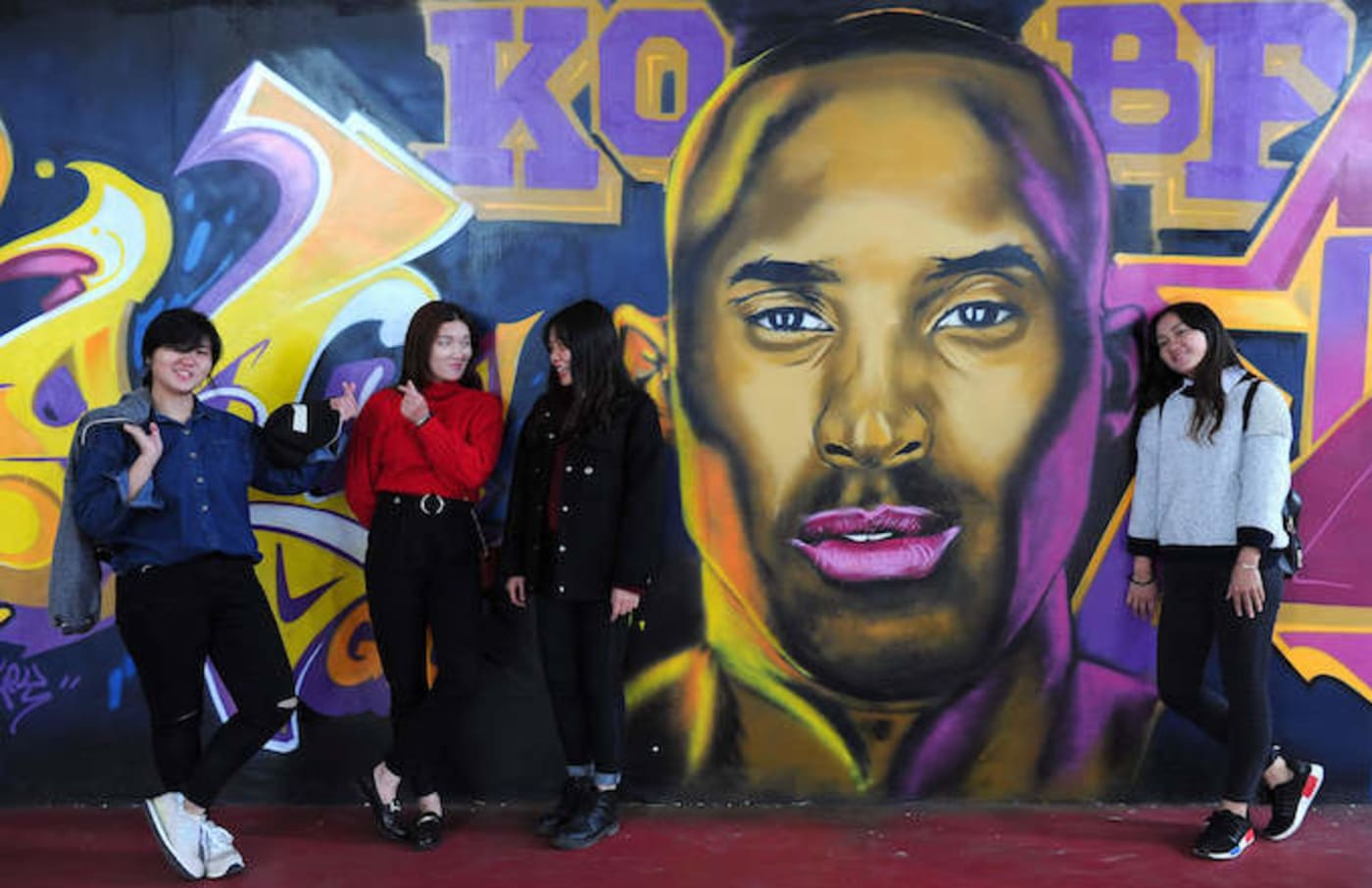 Kobe Bryant mural with young adults